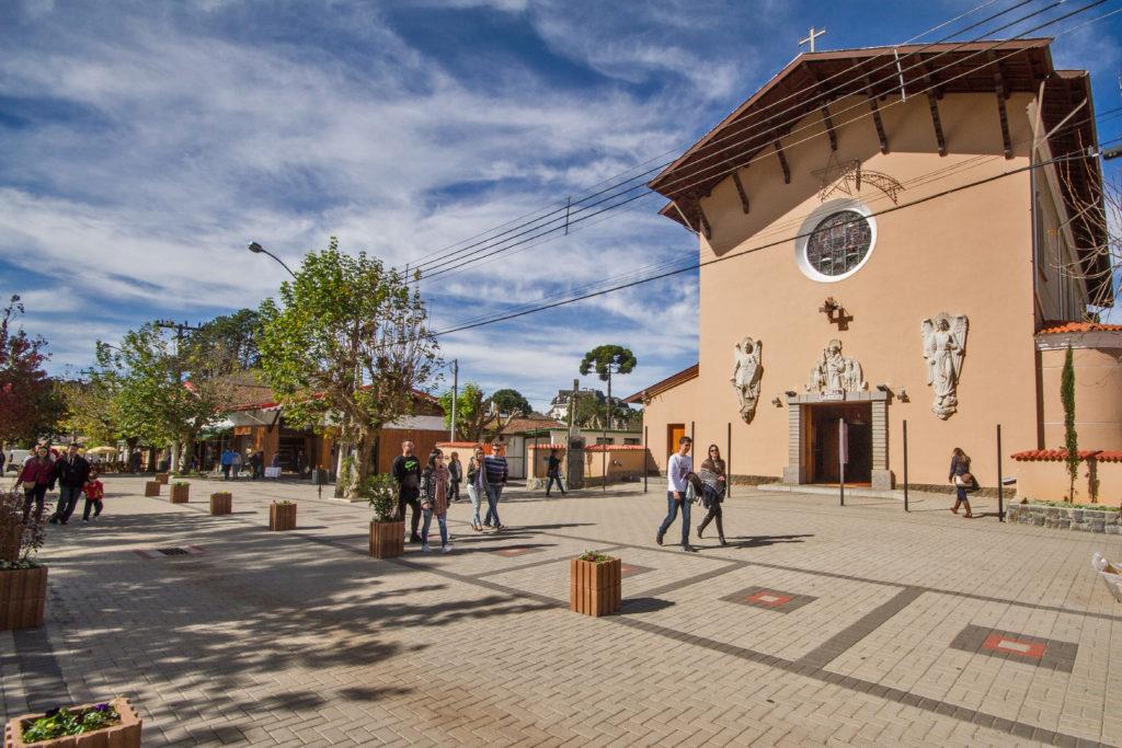 Imagem da Igreja de São Benedito, no Centro do Capivari, Campos do Jordão -SP, com pouco movimento em um dia ensolarado.