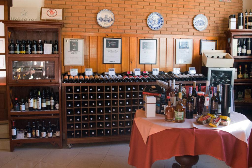 A imagem mostra parte da adega do Empório Vila Chã e uma mesa repleta de produtos tradicionais.